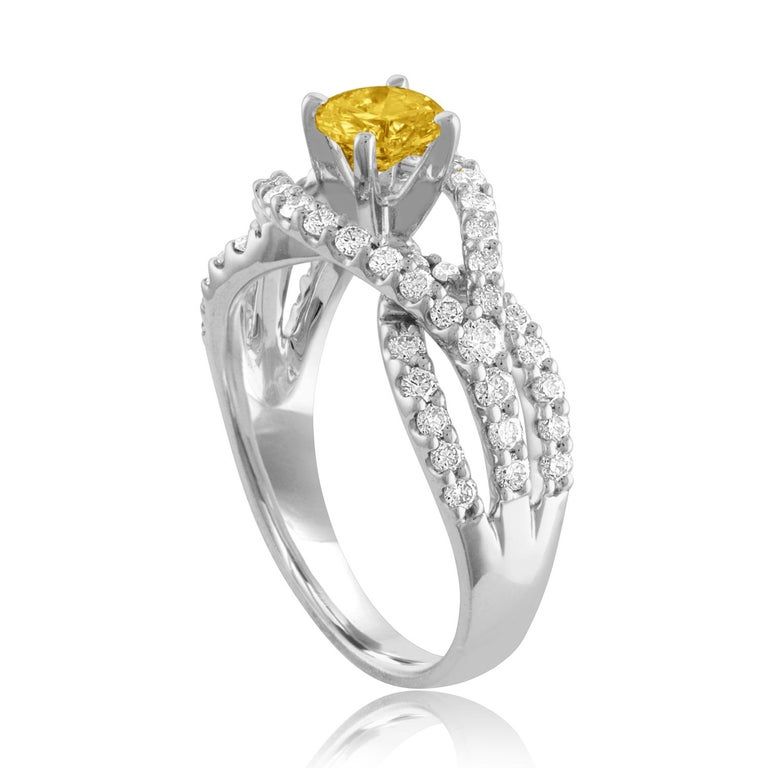 Beautiful Twist Shank Ring The ring is 18K White Gold The Center Stone is a Round Yellow Sapphire 0.59 Carats The Sapphire is AGL Certified Heated There are 0.78 Carats in Diamonds F/G VS/SI The ring is a size 6.75, sizable The ring weighs 5.1 grams