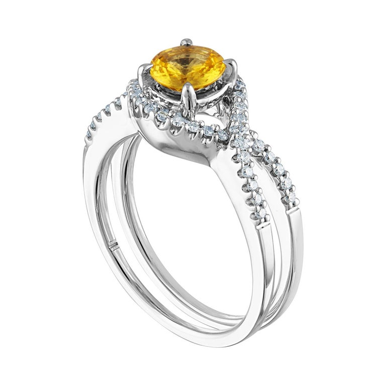 Beautiful Twist Shank Ring The ring is 18K White Gold The Center Stone is a Round Yellow Sapphire 0.77 Carats The Sapphire is AGL Certified Heated There are 0.36 Carats in Diamonds F/G VS/SI The ring is a size 6.00, sizable The ring weighs 5.3 grams