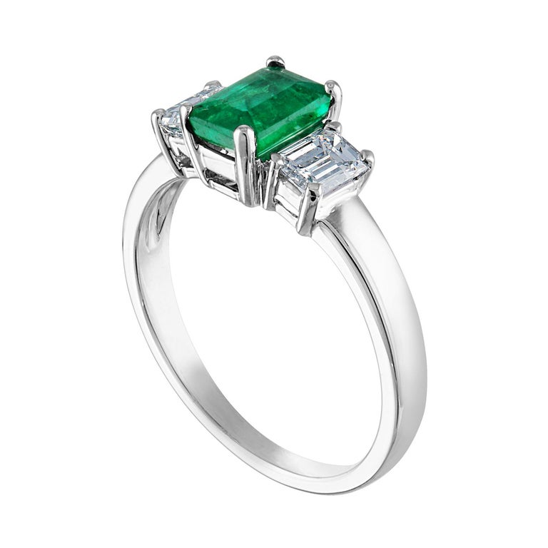 Beautiful 3 Stone Emerald Ring The ring is 18K White Gold. The Center is a beautiful emerald cut 0.84 Carat Emerald. The Emerald is AGL certified. There are 2 side stones 0.64 Carats Diamonds F/G VS/SI The ring is a size 6.75, sizable. The ring