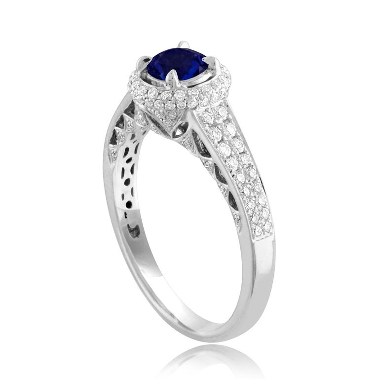 Beautiful Round Halo Pave Ring The ring is 18K White Gold The Center Stone is a Round Blue Sapphire 0.91 Carats The Sapphire is AGL Certified Heated There are 0.49 Carats in Diamonds F/G VS/SI The ring is a size 7.00, sizable The ring weighs 3.9