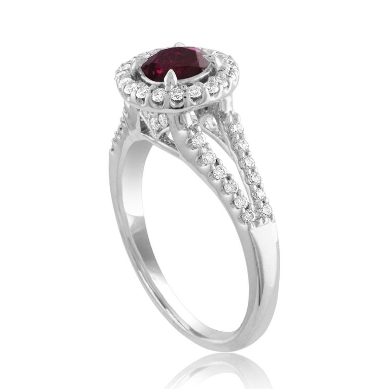 Beautiful Round Halo Split Shank Ring The ring is 18K White Gold The Center Stone is a Round Ruby 1.00 Carats The Ruby is AGL Certified Heated There are 0.33 Carats in Diamonds F/G VS/SI The ring is a size 6.5, sizable The ring weighs 4.4 grams