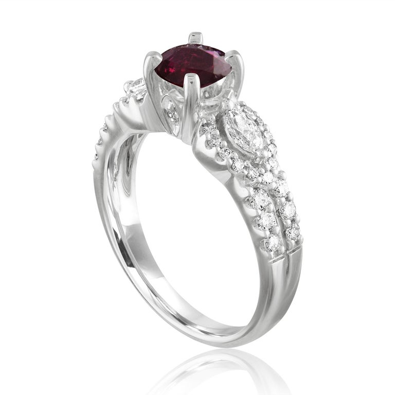 Beautiful Round Halo Split Shank Ring The ring is 18K White Gold The Center Stone is a Round Ruby 1.02 Carats The Ruby is AGL Certified Heated There are 0.50 Carats in Diamonds F/G VS/SI The ring is a size 6.5, sizable The ring weighs 5.4 grams