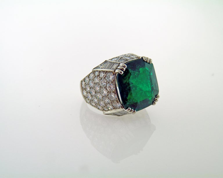A beautiful cocktail ring centering on a cushion-cut emerald weighing 11.38 carats. The emerald is accompanied by the AGL certificate stating that it's of Colombian origin with no indication of clarity enhancement (no oil), The emerald is surrounded