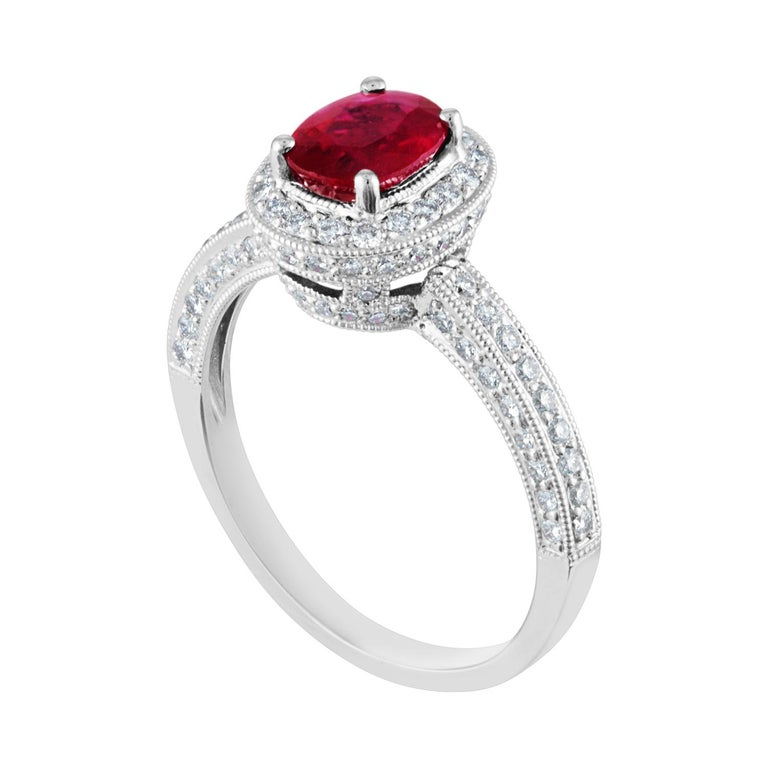 Oval Halo Milgrain Engagement Ring The ring is 18K White Gold The oval Burma ruby is 1.29 Carats There are 0.75 Carats In Diamonds G/H SI The ring weighs 4.2 grams The ring is a size 8.0, sizable