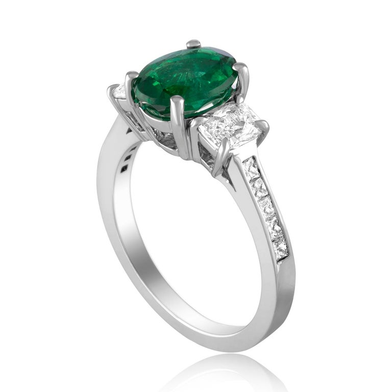 Beautiful Three Stone Emerald Ring The ring is 18K White Gold. There are 2 side stones 0.62 Carats Diamonds F VS The Band has small princess cut diamonds 0.23 Carats F VS The Center is a beautiful oval 1.55 Carat Emerald. The Emerald is AGL