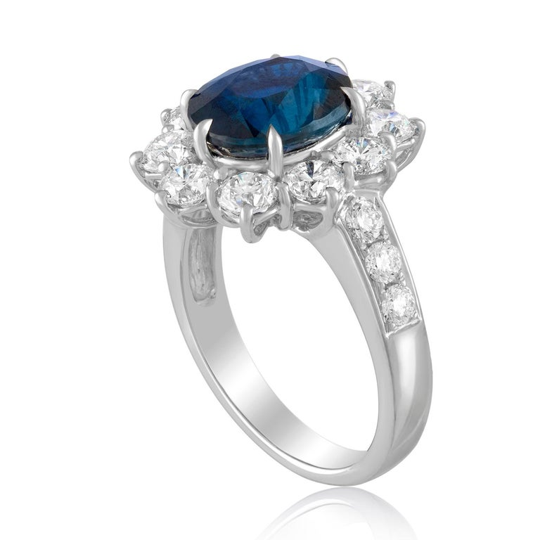 Beautiful Classic Oval Halo Ring. The ring is 18K White Gold. The ring has 2.13 Carats in Diamonds F VS. The center stone is an oval shaped 4.07 Carat Blue Sapphire. The Sapphire is certified by AGL, NO HEAT. The top of the ring measures 17.67 mm x