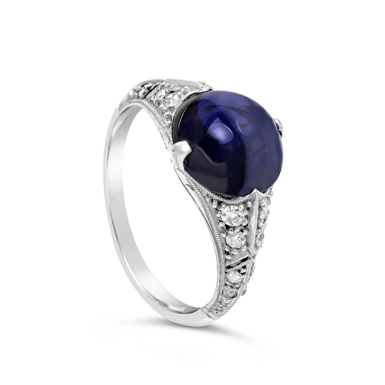 A gorgeous and color-rich cabochon sapphire weighing 4.20 carats, set in an antique art deco style platinum band accented with round diamonds. AGL certified the cabochon sapphire.