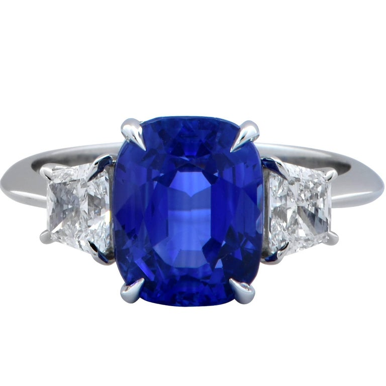 This gorgeous three-stone platinum ring features an AGL graded 4.85ct Cyelon no heat sapphire and is accented by two trapezoid cut diamonds weighing .81cts G color VS clarity.  The ring is a size 6 and can be sized up or down. Measurements are
