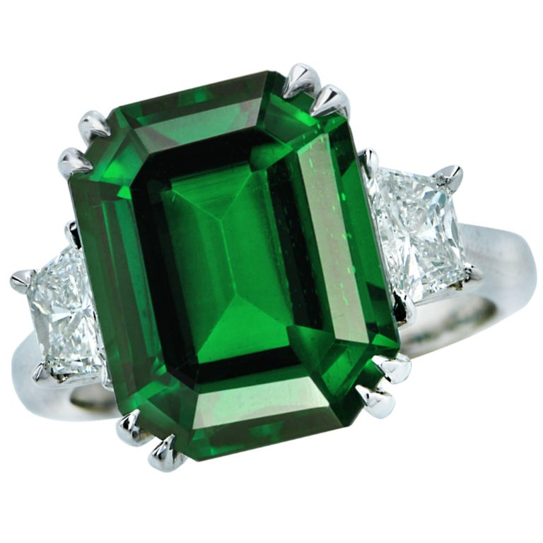 Feast your eyes on this stunning rich verdant green emerald cut Tsavorite Garnet weighing 9.79ct, complimented by 2 trapezoids weighing .77cts F color and VS clarity set in platinum. This custom made ring is a size 5.5. The face measures 13.3mm by