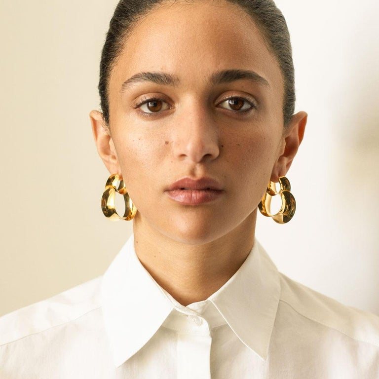 AGMES Gold Vermeil Double Hoop Layered Curve Earrings. Gold Vermeil post. Handmade in New York City. Inspired by urban landscapes, architecture and modern art, the collection creates a feminine geometry expressed through clean lines and sculptural