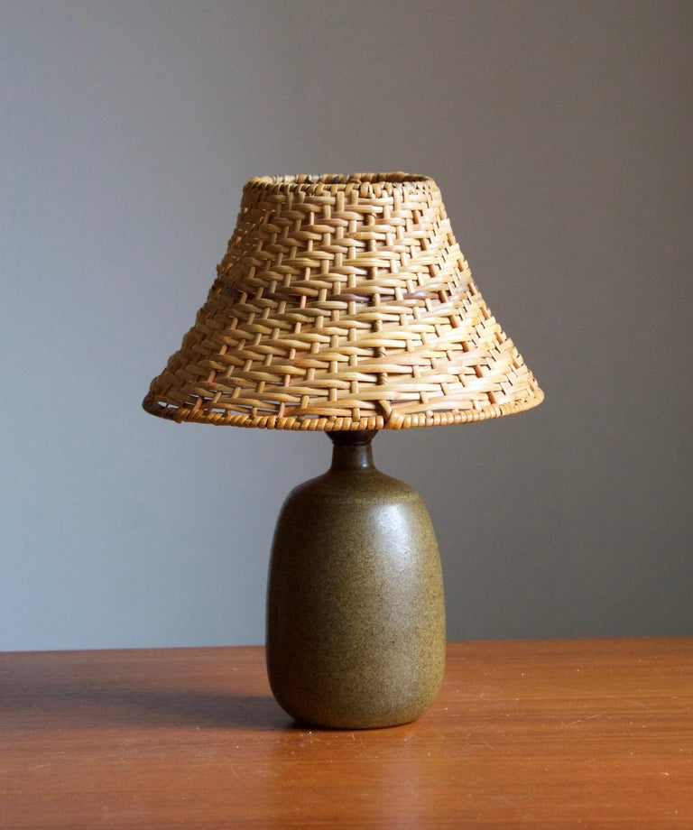 A stoneware table lamp, executed by Agne Aronsson. In his studio. Signed. Features green glaze and very subtle decor.   Stated dimensions exclude lampshades. Illustrated model vintage rattan lampshade can be included in purchase upon