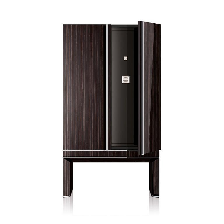 Armored armoire in polished ebony, brass accessories in Ruthenium. Safe with biometric opening device, drawers and trays lined for watches and jewelry. Available with 18 Swiss made watch winders. Two secret compartments. Safe to be anchored to the