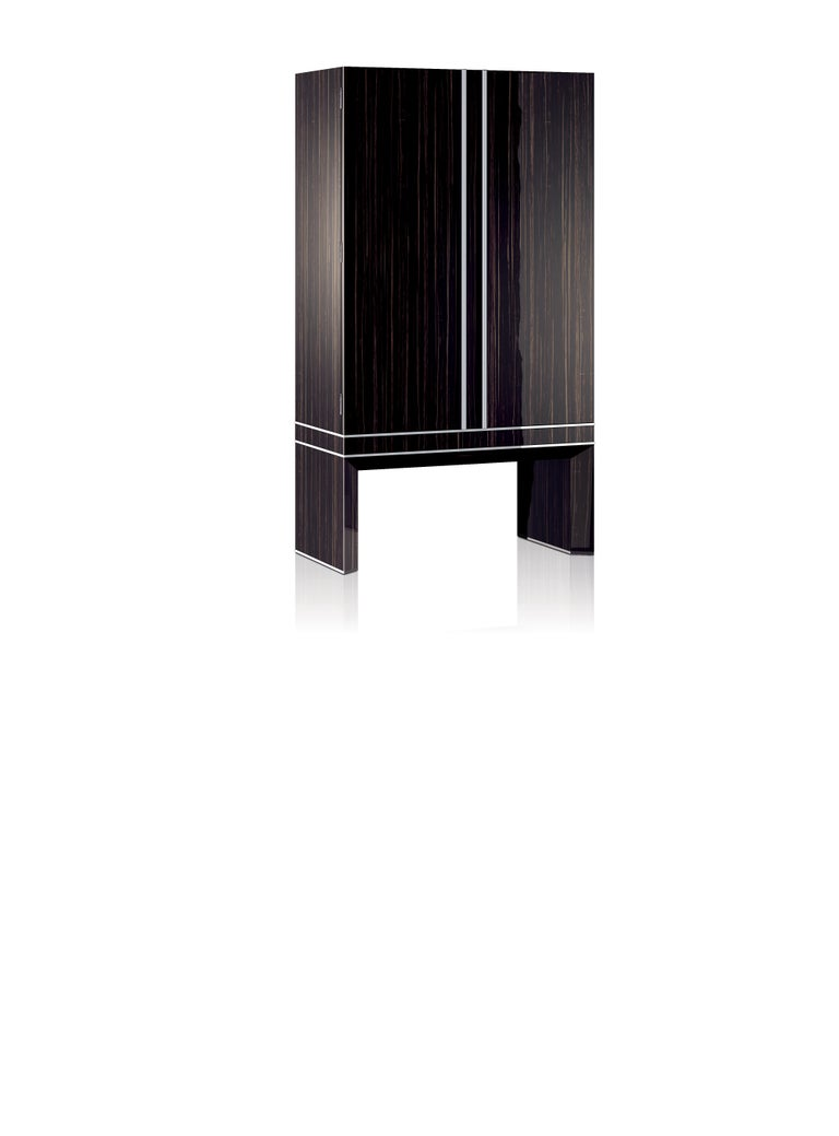 Armored armoire in polished ebony, brass accessories in ruthenium. Safe with biometric opening device, drawers and trays lined for watches and jewelry. Available with 36 Swiss made watch winders. Two secret compartments. Safe to be anchored to the