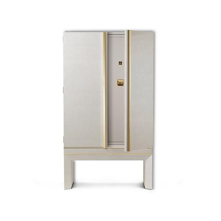Armoured jewelry armoire in polished white bird's-eye maple and 24-karat gold hardware. Inside, safe with biometric opening device. Drawers and pull-out trays lined for jewelry. Six watch winders made in Switzerland and secret compartment.