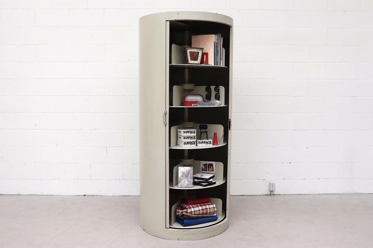 Rare industrial storage unit with 5 rotating shelves and sliding door. Cylindrical grey enameled metal frame in very original condition with visible signs of wear including some denting, scratching and light surface rust and enamel loss.