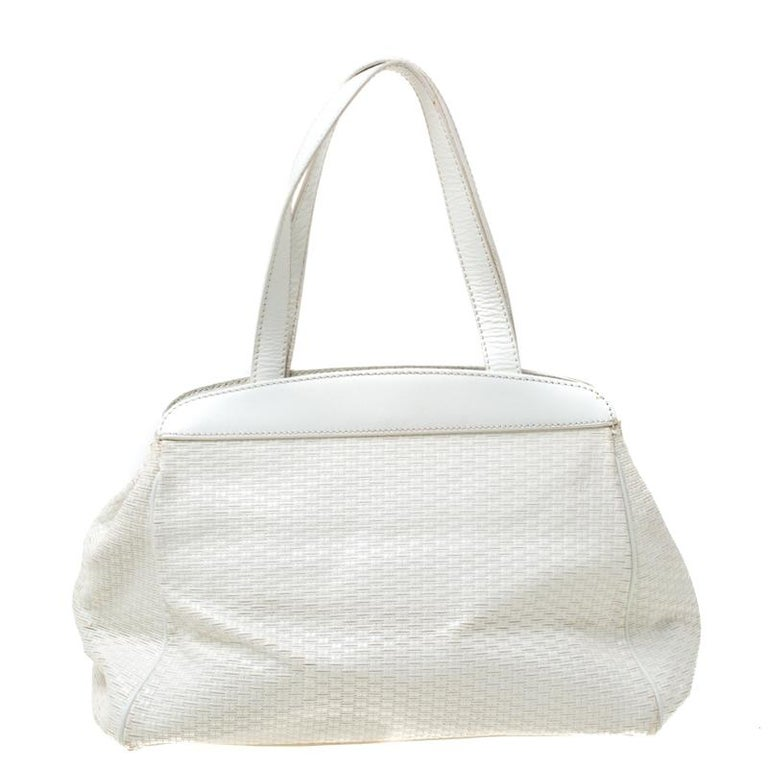 This stunning satchel is by Aigner. Crafted from off-white leather, the bag features weave patterns, two handles, and a spacious fabric interior. Place it in your arms to lend your outfit the appropriate measure of class and style.  Includes: The