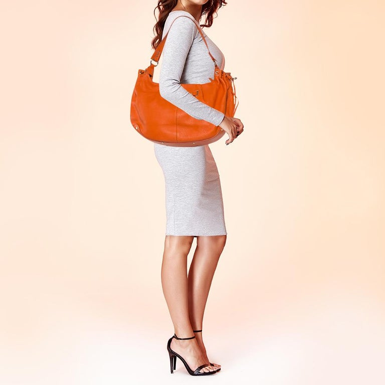 Simple, polished, and extremely luxurious with a contemporary edge, this Aigner orange leather bag stands out due to its bright color and structured shape. Made with incredible interior lining, this eye-catching statement piece will heighten any