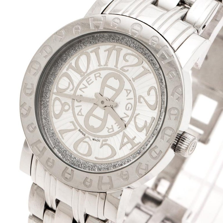 Aigner is considered the first voguish brand for stylish living from Germany. This silver stainless steel women's wristwatch by Aigner is a fashionable example of the aforementioned. The watch features a fancy round bezel with Aigner's signature