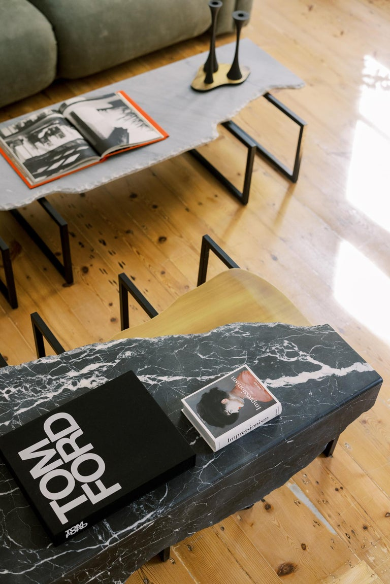 Coffee tabletop in polished Patagonia granite with a split face effect on the edge and an inlay metal detail in dark oxidized brass with a high-gloss finish. Metal structure base lacquered in satin black.  Aire coffee table Medium  FI007 black