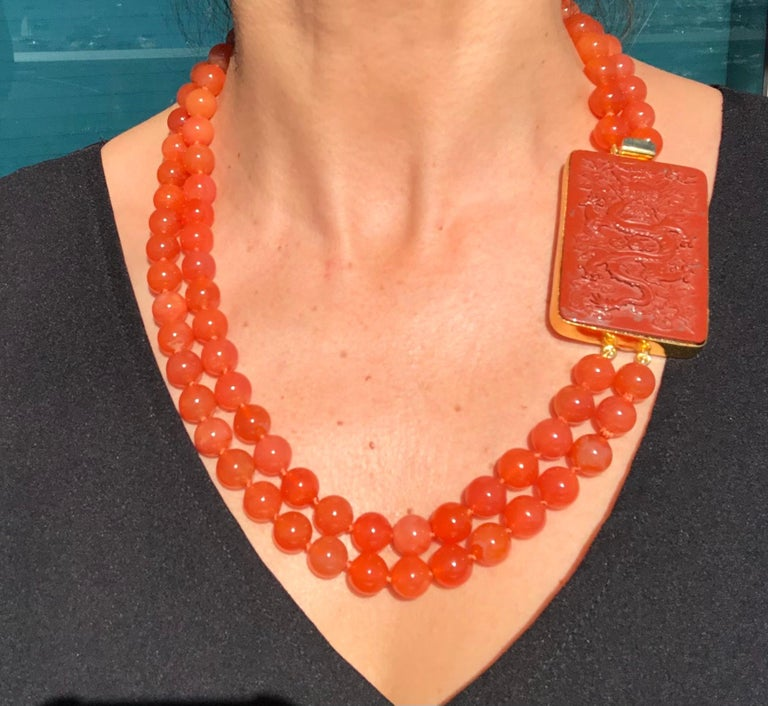 One-of-a-Kind A beautiful Aventurine Dragon inset in a Sterling Silver box clasp connects a double strand of 10mm brilliant rusty orange Carnelian beads in a matinee length necklace. Silk hand-knotted Approx: 22 inches to 24 inches