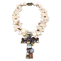 A.Jeschel Precious stone encrusted Silver Cross anchors a Pearl Necklace.