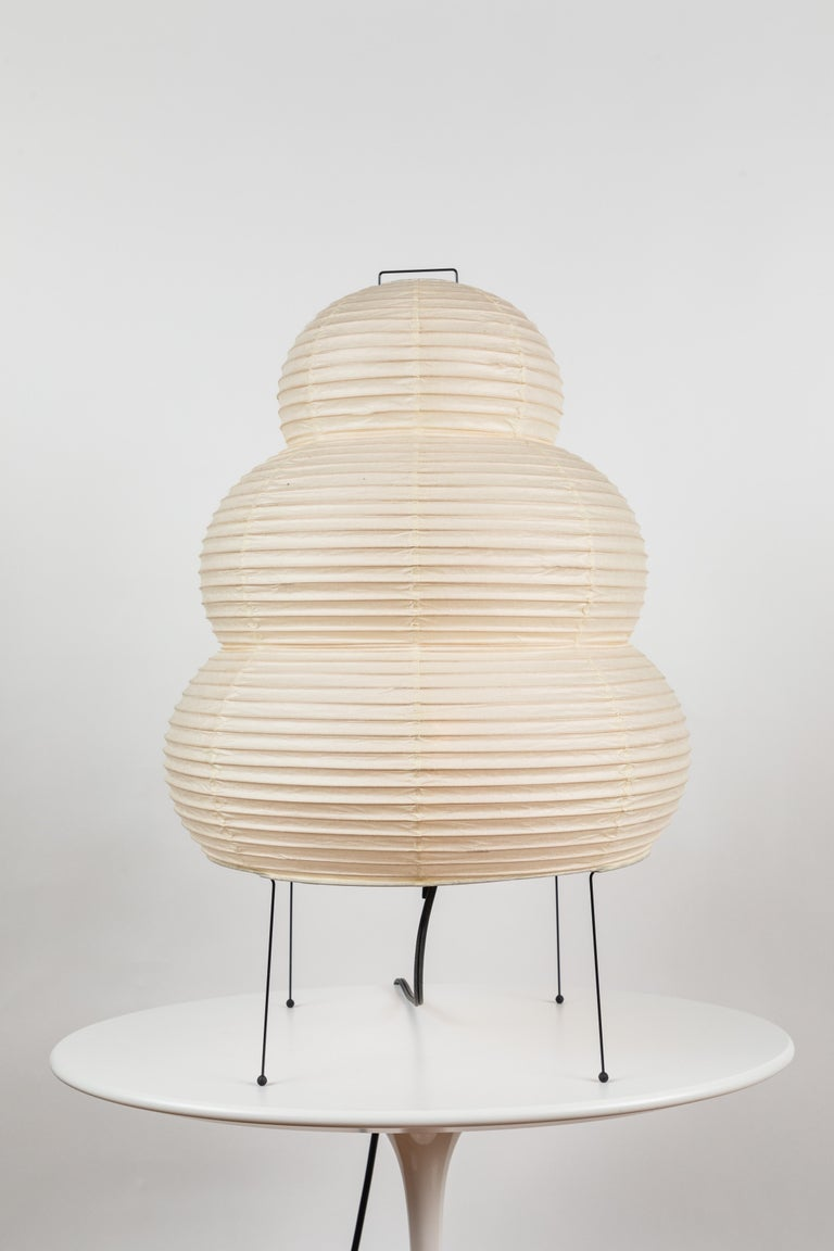 Akari model 24N light sculpture by Isamu Noguchi. The shade is made from handmade washi paper and bamboo ribs with Noguchi Akari manufacturer's stamp. Akari light sculptures by Isamu Noguchi are considered icons of 1950s modern design. Designed by