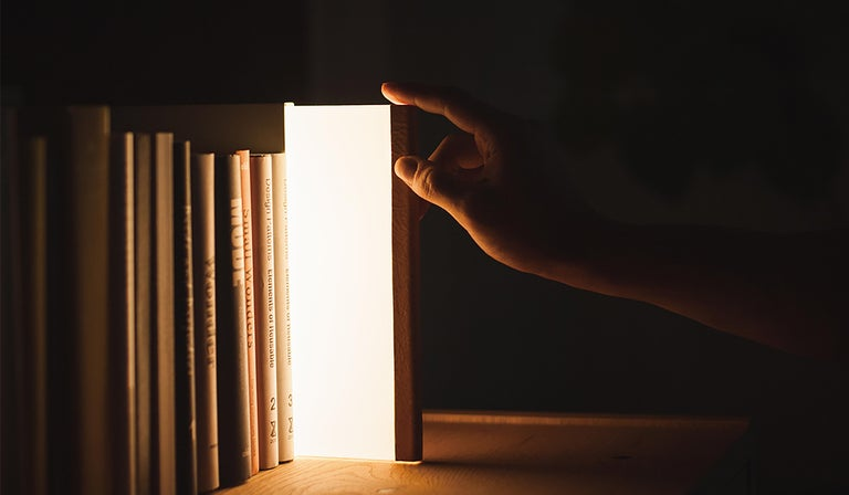 """Steel / aluminum / acrylic / leather  White  Measures: 8.5"""" H x 6"""" W x .6"""" D  4w LED   AC adapter (AC100-240V)  Design by Naoaki Iwamatsu and Takaaki Maeda   Designed to blend into the bookshelf as an elegant leather-spined volume in a"""