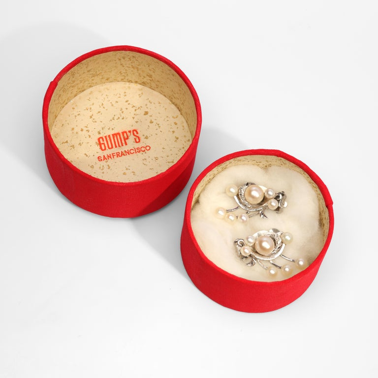 These early 1950s earrings from Gump's of San Francisco were hand-crafted in Japan from silver and cultured Akoya pearls. Created as figural floral sprays, each earring is anchored by a large 7mm pearl surrounded by six 5mm pearls on silver