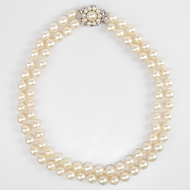 This double strand of cultured Akoya pearls was created in the 1950s and features large —9.00-9.40mm— pearls with thick, luscious nacre. The pearls are light cream with rose overtones. The silver clasp features an 8.5mm pearl surrounded by a halo of