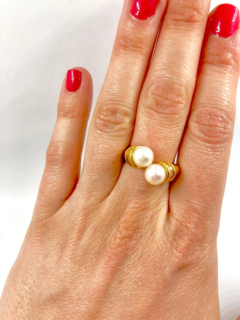 A yellow gold bypass ring set with two akoya pearls surrounded by brilliant cut diamonds. Pearls Diameter: 6,5 Total Diamonds Weight: 0.15 carat Net Weight: 4.90 grams Finger size: 6 can be sized