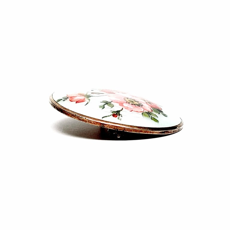 Gold vermeil over sterling silver round enameled pin with flowers by Aksel Holmsen, circa 1950s.  Beautiful white guillouche enamel painted with pink flowers and green leaves.  Measures approx 1 1/2
