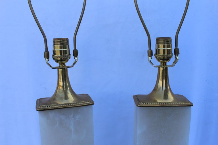 A pair of deco modern looking lamps. Made from solid blocks of Alabaster from Spain. Designed by a LA Lighting Designer . Metal is solid hi-polished brass. Single socket. Showroom samples, never used. Measures: 27 3/4