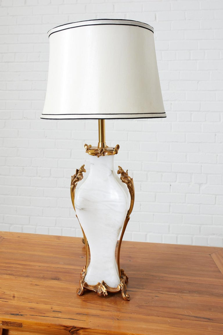Stunning Alabaster table lamp by Marbro Lamp Company featuring a brass base tinted in rose gold with climbing acanthus and matching top. This special order lamp weighs over twenty pounds with hardware and finial. The lamp has been stamped and