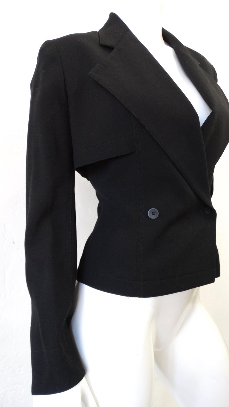 Elevate your look with this amazing Alaia blazer! Circa 1980s, this black double breasted blazer is crafted from 100% Wool and features long sleeves with slits at the cuff and a large notched collar with a cropped section of fabric around the back.