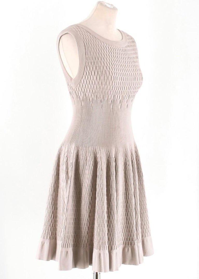 Alaia Beige Stretch Knit Dress  -Beige stretch knit dress  -Classic fit and flare silhouette -Back zip closure -Scoop neckline  Please note, these items are pre-owned and may show signs of being stored even when unworn and unused. This is reflected