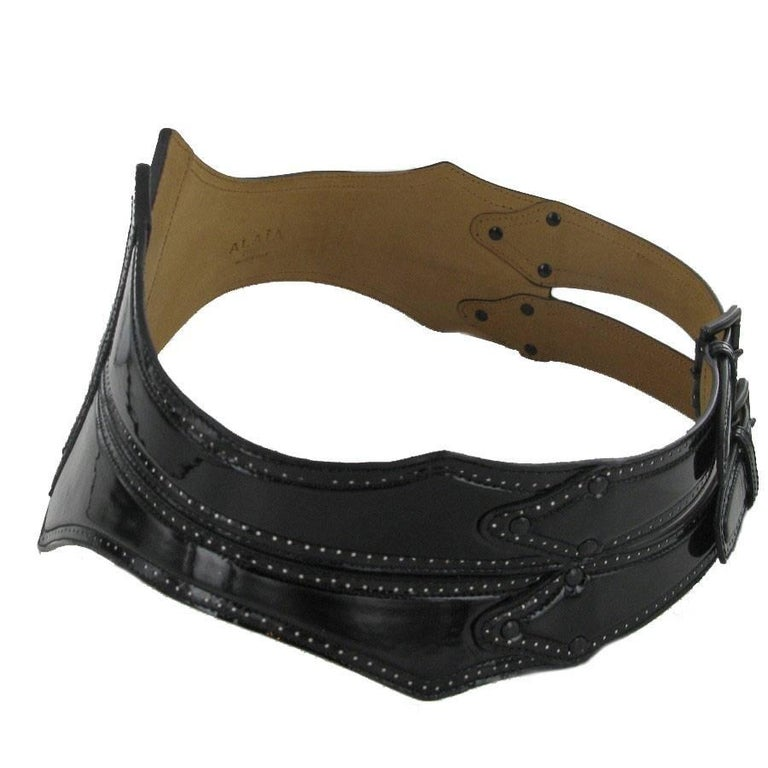 Beautiful ALAIA black patent leather belt. Ultra trendy collector's item. It is Perforated black patent leather. 2 buckles in gunmetal color.  2 water stains on the inside of the belt. Size 85  Dimensions : Length: 92 cm, Width: 16.5 cm