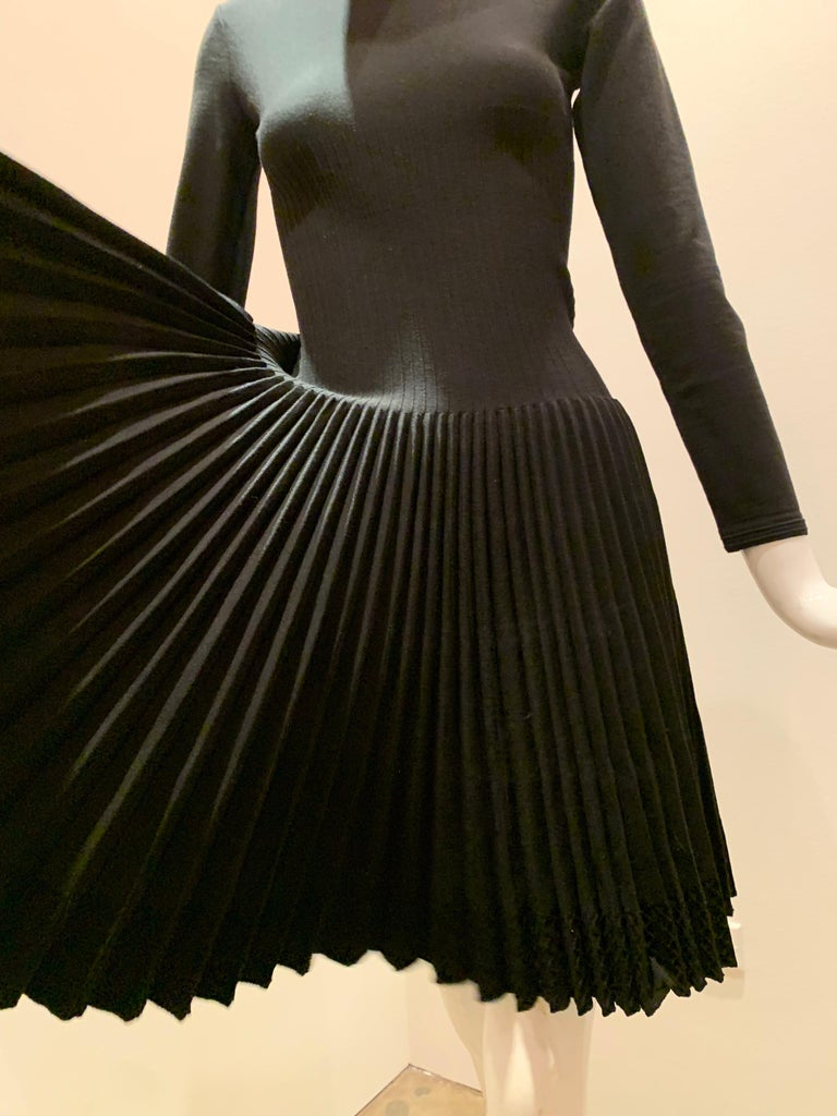 A wonderful basic from Azzedine Alaia:  A blackwool knit dress with a high crew banded neckline, 3/4 sleeves, a dropped waist and a full pleated skirt.  Zippered back.