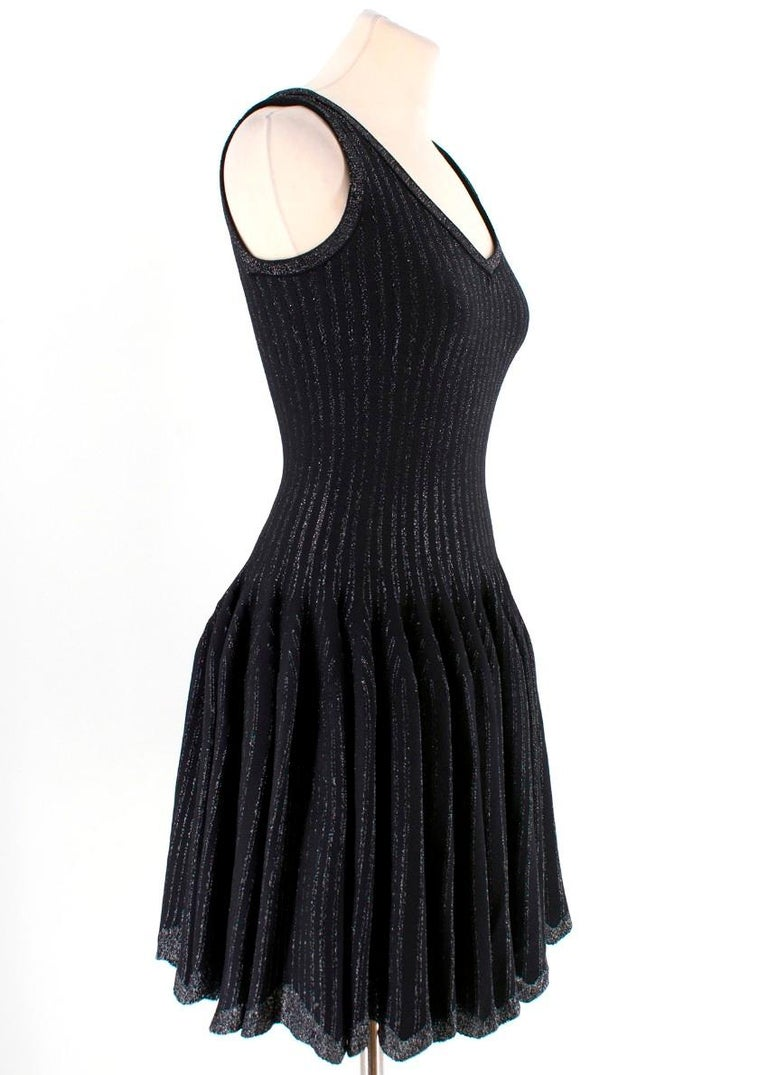 Alaia Black with Silver Stripes Dress  -Alaia dress with silver tone accent stripes -Sparkle neckline, straps and hemline -Pleated skirt -Scalloped hemline -Hidden back zip -V neck  Please note, these items are pre-owned and may show signs of being