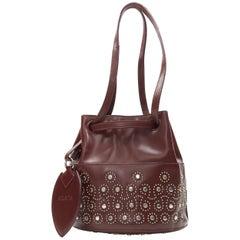 ALAIA burgundy red geometric silver studded drawstring mirror charm bucket bag