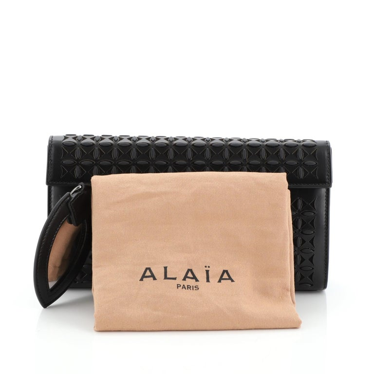 This Alaia Flap Clutch Laser Cut Leather Small, crafted in black laser-cut leather, features gunmetal-tone hardware. Its magnetic closure opens to a neutral leather interior with slip pocket.  Estimated Retail Price: $1,970 Condition: Very good.