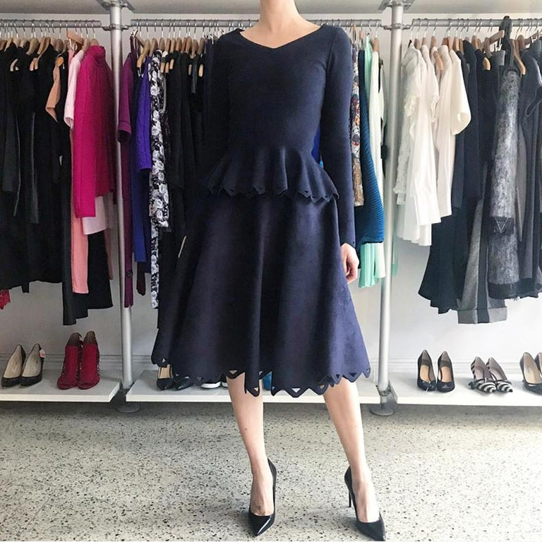 Alaia Navy Velour 2pc Perforated Skirt and Peplum Top Set.  Full circle skirt with cut out hem design.  Top has a V neckline with ¾ sleeves, centre back zipper, and peplum.  Material is a heavy stretch knit with fuzzy velour top and thick knit base.