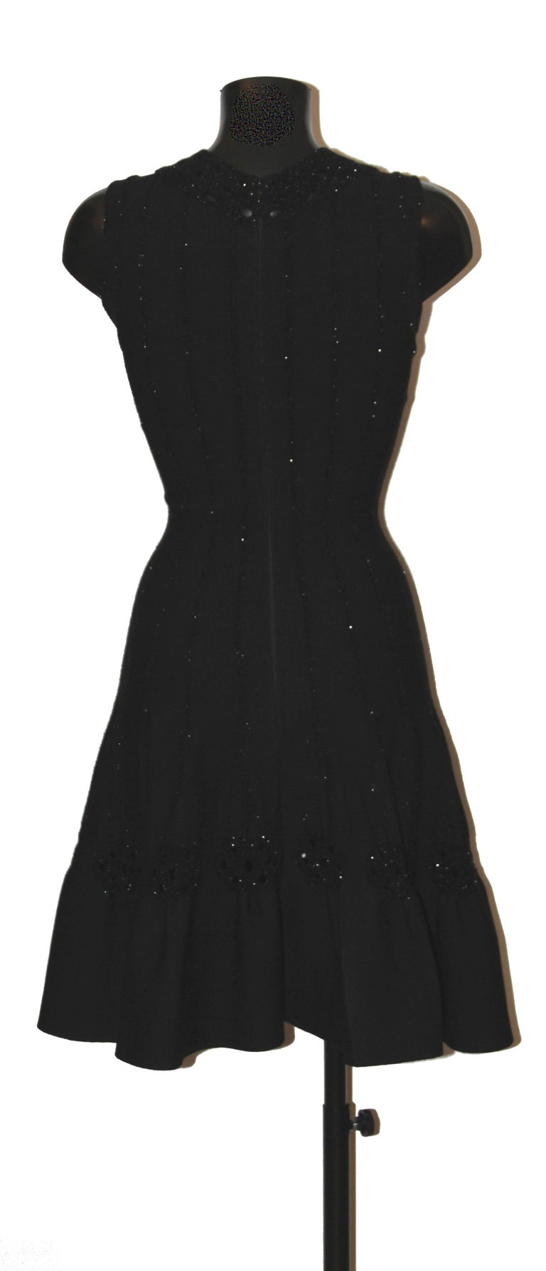 This beautiful pre-owned black wool stretch flared sleeveless dress from Azzedine Alaïa features black and silver lurex laced trim all around and throughout the dress. Fit and flare, it has a V-neckline and a concealed zip down back.  Fabric: 65%