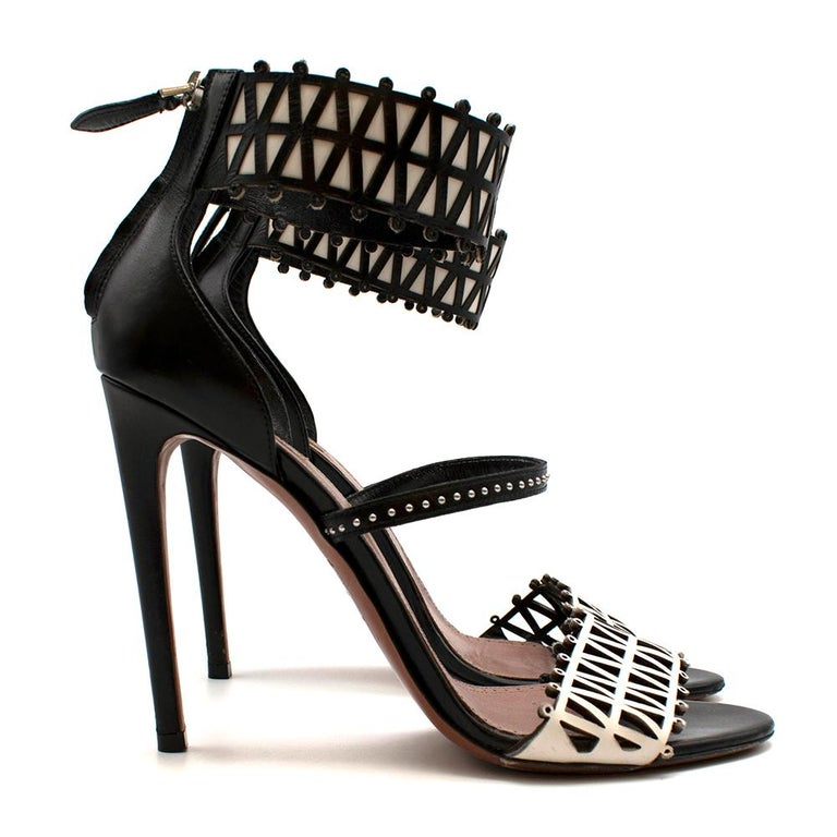 Alaia Stiletto Black & White Lasercut Sandals  - Size 40 = UK 7 - Laser cut design on the front of the toes - Large ankle strap with white leather contrast - Mid ankle strap with silver studs - Back zip attachment with silver hardware - Tall