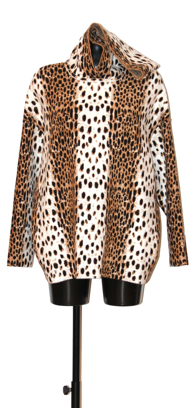 This pre-owned but New hooded sweatshirt from Azzedine Alaïa features a leopard motif print. The fabric mix is extremely soft to the touch. 40% Viscose 35% Polyamide 23% Wool 2% Elastane  Its size is 36 but oversize cut.  All items are subject to a
