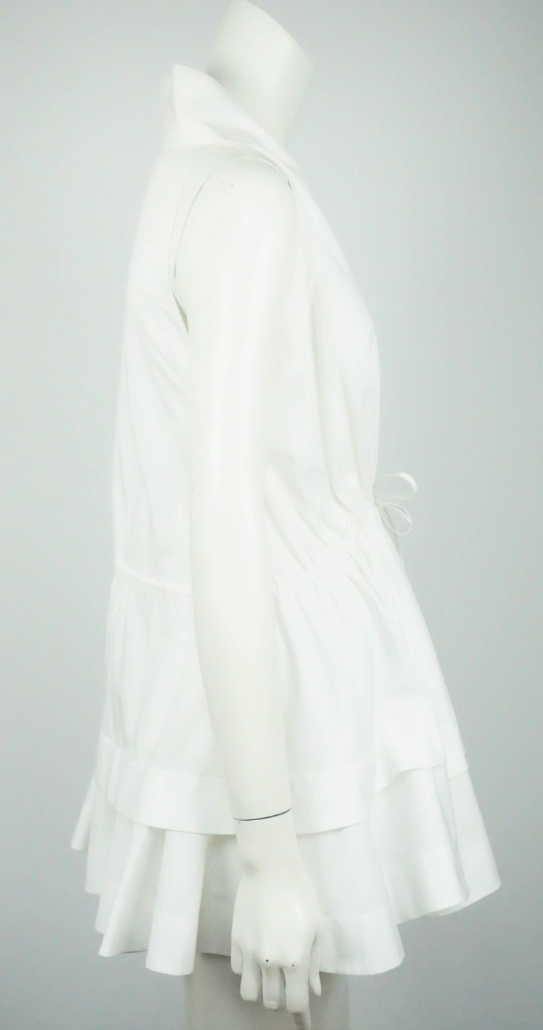 Alaia White Cotton Long Top - 42 This elegant Alaia piece is made of cotton and polyester. It is a white sleeveless, draw string at the waist top, v-neck and a flare skirt with trim detail at the bottom. It has a slight cross over effect with a