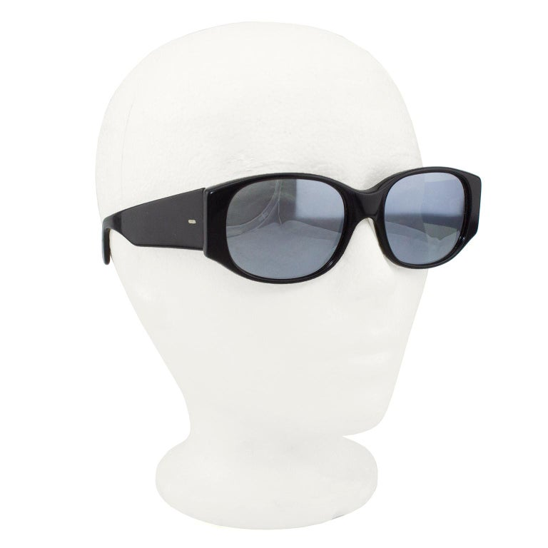 Futuristic styled sunglasses with mirrored lenses from famed glasses designer Alain Mikli. All black frames with thick arms. Slight mirror loss on lenses. In very good condition.   Length 6
