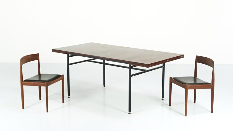 Modernist dining table, by French designer Alain Richard and manufactured by Meubles TV during the 50's. It consist on a rosewood veneered table top, with two extensions, supported by a black lacquered square shaped tubular steel base, enhanced by
