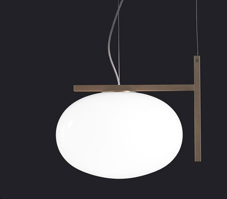 Alba suspension lamp designed by Mariana Pellegrino Soto for Oluce. The shape of the lamp resembles a drop of water, bringing the world of nature into this design. This lamp rests on a frame of satin brass that gives the lamp a modern look but also