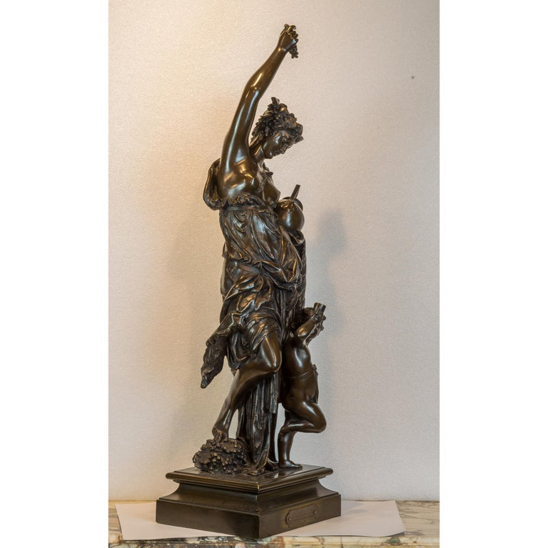 Modeled as a bacchanalian maiden holding aloft a bunch of grapes and a jug in the other, accompanied by a putto holding a horn cup, on square base, incised A. CARRIER-BELLEUSE, with applied title plaque to front.  Maker: Albert Carrier-Belleuse