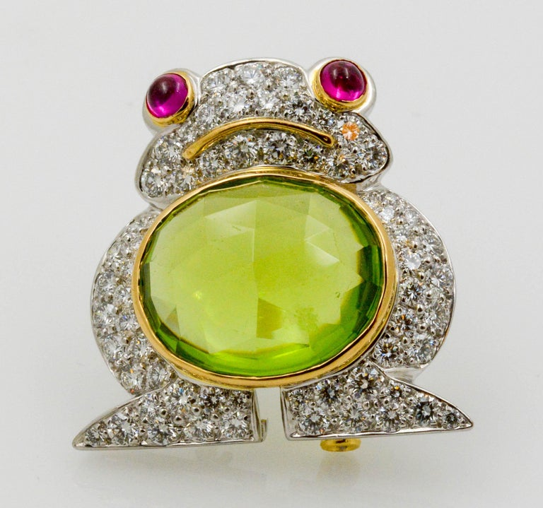 Designer Albert Lipten created this charming platinum and 18 karat white gold frog brooch set with a 4.30 carat oval Peridot and surrounded with 62 round brilliant cut diamonds (2.50 carats total weight) and two (2) ruby cabochons eyes (0.40